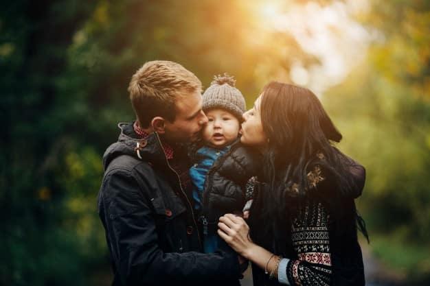 parents-embrassent-enfant-dans-parc soins energetiques Nantes les bienfaits d un soin energetique pour un bebe